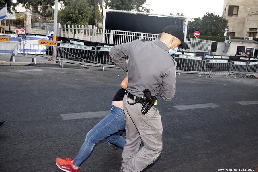 שוטרים גוררים מפגינה על רקע הוילון